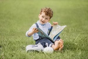 Child reading book outside